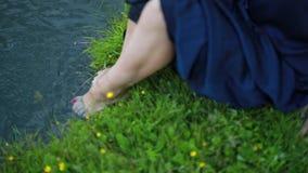 Το πράσινο κορίτσι όχθεων ποταμού πλένει τα πόδια της απόθεμα βίντεο