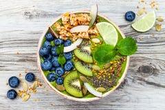 Το πράσινο κύπελλο καταφερτζήδων προγευμάτων τσαγιού Matcha superfoods που ολοκληρώνεται με τους σπόρους chia, λιναριού και κολοκ Στοκ Φωτογραφία