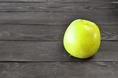 Το πράσινο μήλο βρίσκεται σε έναν ξύλινο πίνακα στοκ φωτογραφία