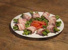 Το πράσινο φασόλι κυλά στο μπέϊκον στο άσπρο πιάτο με την τεμαχισμένη ντομάτα στο W Στοκ φωτογραφία με δικαίωμα ελεύθερης χρήσης