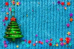 Το πράσινο χριστουγεννιάτικο δέντρο παιχνιδιών γυαλιού και τα ζωηρόχρωμα αστέρια σε ένα μπλε πλέκουν Στοκ φωτογραφία με δικαίωμα ελεύθερης χρήσης