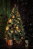 Το πράσινο χριστουγεννιάτικο δέντρο που διακοσμείται με τους χρυσούς κίτρινους κώνους διακοσμεί κοντά στον καφετή τοίχο στο σκοτά στοκ εικόνα