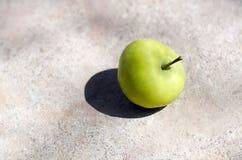 Το πράσινο juicy ώριμο μήλο βρίσκεται σε ένα άσπρο λάμποντας πάτωμα τσιμέντου υπαίθριο Στοκ Φωτογραφίες