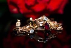 Το πραγματικό χρυσό δαχτυλίδι με το διαμάντι, αλυσοδένει κοντά επάνω το μακρο πυροβολισμό στην απεικόνιση της μαύρης λαμπρής επιφ στοκ φωτογραφία
