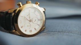 Το πρακτικό και η κίνηση από δεύτερο χέρι, περιστρέφονται σε ένα wristwatch με ένα λουρί που βρίσκεται σε μια μπλε επιφάνεια υφάσ φιλμ μικρού μήκους