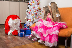 Το πριόνι δύο κοριτσιών που Άγιος Βασίλης βάζει παρουσιάζει κάτω από το χριστουγεννιάτικο δέντρο Στοκ φωτογραφία με δικαίωμα ελεύθερης χρήσης