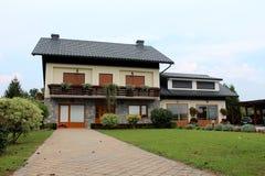 Το προαστιακό οικογενειακό σπίτι με την πέτρα κεραμώνει driveway και το νέο γκαράζ που περιβάλλονται με την πρόσφατα κομμένη πράσ στοκ εικόνες