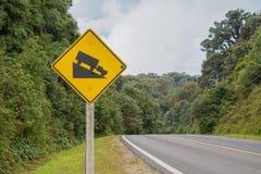 Το προειδοποιώντας απότομο οδικό σημάδι και χύνει Στοκ Εικόνες