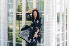 Το προκλητικό έξυπνο κορίτσι στο μετάξι ντύνει την τοποθέτηση ενάντια στους stained-glass τοίχους ενός ακριβού εστιατορίου Η γυνα στοκ εικόνα