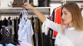 Το προκλητικό κορίτσι, ψηλή, όμορφη ξανθή γυναίκα επιλέγει τα ενδύματα στο κατάστημα Αγορές σε ένα μοντέρνο κατάστημα ιματισμού κ απόθεμα βίντεο
