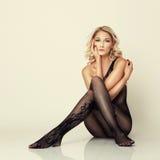 Το προκλητικό ελκυστικό κορίτσι στις γυναικείες κάλτσες θέτει στο πάτωμα Στοκ φωτογραφία με δικαίωμα ελεύθερης χρήσης