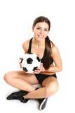 Το προκλητικό κορίτσι κάθεται με μια σφαίρα ποδοσφαίρου σε ένα άσπρο υπόβαθρο FR Στοκ εικόνες με δικαίωμα ελεύθερης χρήσης