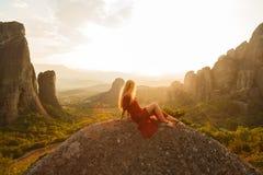 Το προκλητικό κορίτσι κάθεται στην άκρη του απότομου βράχου και της εξέτασης την κοιλάδα και τα βουνά ήλιων Στοκ Φωτογραφίες