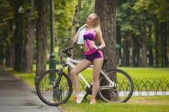 Το προκλητικό κορίτσι με το νερό και την πετσέτα στέκεται κοντά στο ποδήλατο Στοκ Εικόνες