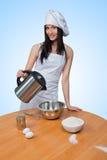 Το προκλητικό κορίτσι που φορά τον αρχιμάγειρα προετοιμάζει τη ζύμη στοκ φωτογραφίες