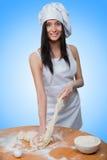 Το προκλητικό κορίτσι που φορά τον αρχιμάγειρα προετοιμάζει τη ζύμη στοκ εικόνες