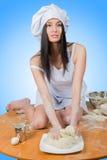 Το προκλητικό κορίτσι που φορά τον αρχιμάγειρα προετοιμάζει τη ζύμη στοκ εικόνες με δικαίωμα ελεύθερης χρήσης