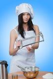 Το προκλητικό κορίτσι που φορά τον αρχιμάγειρα προετοιμάζει τη ζύμη στοκ φωτογραφία με δικαίωμα ελεύθερης χρήσης