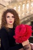 Το προκλητικό κορίτσι σε ένα μαύρο φόρεμα με το κόκκινο αυξήθηκε Στοκ εικόνα με δικαίωμα ελεύθερης χρήσης