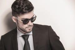 Το προκλητικό νέο επιχειρησιακό άτομο που φορά τα γυαλιά ηλίου κοιτάζει μακριά στοκ εικόνα με δικαίωμα ελεύθερης χρήσης