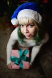 Το προκλητικό νέο κορίτσι δίνει το δώρο κάτω από το χριστουγεννιάτικο δέντρο Στοκ Εικόνες