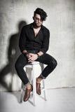Το προκλητικό πρότυπο ατόμων μόδας έντυσε την περιστασιακή τοποθέτηση δραματική ενάντια στον τοίχο grunge Στοκ Φωτογραφία