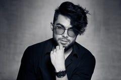 Το προκλητικό πρότυπο ατόμων μόδας έντυσε την περιστασιακή τοποθέτηση γυαλιών φθοράς δραματική ενάντια στον τοίχο grunge Στοκ Εικόνες