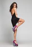 Το προκλητικό πρότυπο γυναικών με τα μακριά πόδια στο μαύρο φόρεμα στο στούντιο στοκ εικόνα