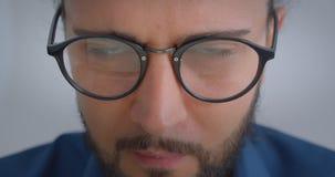 Το προοδευτικό καυκάσιο freelancer eyeglasses με το ponytail που είναι συγκεντρωμένες στροφές κοιτάζει στη κάμερα και τα χαμόγελα απόθεμα βίντεο