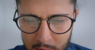 Το προοδευτικό καυκάσιο freelancer eyeglasses με το ponytail που είναι συγκεντρωμένες στροφές κοιτάζει στη κάμερα και τα χαμόγελα φιλμ μικρού μήκους