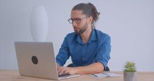 Το προοδευτικό freelancer με το ponytail και eyeglasses που λειτουργούν με το lap-top στο ελαφρύ γραφείο χαμογελά στη κάμερα φιλμ μικρού μήκους