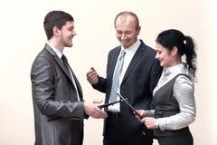 Το προσωπικό συζητά τα επιχειρησιακά έγγραφα, που στέκονται στο λόμπι του γραφείου στοκ εικόνα