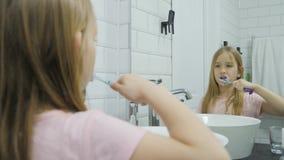 Το προ κορίτσι εφήβων βουρτσίζει τα δόντια και την πλύση της το πρόσωπό του στο λουτρό φιλμ μικρού μήκους