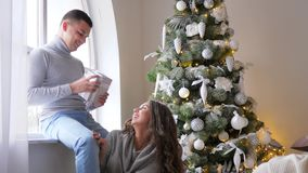 Το πρωί Χριστουγέννων, κορίτσι με το τεχνητό χιόνι στην τρίχα παρουσιάζει ένα δώρο στο σύζυγό της εκτός από το διακοσμημένο χριστ απόθεμα βίντεο