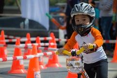 Το πρωτάθλημα Chiangrai ποδηλάτων ισορροπίας βατραχοπέδιλων, παιδιά συμμετέχει στη φυλή ποδηλάτων ισορροπίας Στοκ Εικόνα