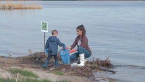 Το πρόβλημα της πλαστικής ρύπανσης, κορίτσι με το αγόρι παιδιών προσφέρεται εθελοντικά την καθαρή βρώμικη ακτή από το πλαστικό κο απόθεμα βίντεο