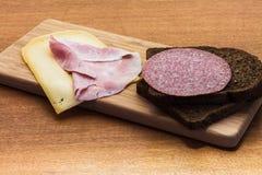Το πρόγευμα ή το μεσημεριανό γεύμα που θέτει με το τυρί ζαμπόν ένα καφετί σάντουιτς πασπαλίζει με ψίχουλα στον ξύλινο πίνακα Στοκ Εικόνα