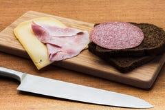 Το πρόγευμα ή το μεσημεριανό γεύμα που θέτει με το τυρί ζαμπόν ένα καφετί σάντουιτς πασπαλίζει με ψίχουλα στον ξύλινο πίνακα Στοκ Εικόνες