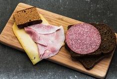 Το πρόγευμα ή το μεσημεριανό γεύμα που θέτει με το τυρί ζαμπόν ένα καφετί σάντουιτς πασπαλίζει με ψίχουλα στον ξύλινο πίνακα Στοκ εικόνα με δικαίωμα ελεύθερης χρήσης