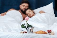 Το πρόγευμα με croissant και αυξήθηκε στο δίσκο στο κρεβάτι και το αγαπώντας ζεύγος στο υπόβαθρο Στοκ εικόνες με δικαίωμα ελεύθερης χρήσης