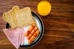 Το πρόγευμα του ζαμπόν, το ποτήρι του χυμού από πορτοκάλι και η κινηματογράφηση σε πρώτο πλάνο Αμερικανός φρυγανιάς προγευματίζου Στοκ Εικόνα