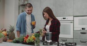 Το πρόγευμα υγείας για μια νεολαία συνδέει το πρωί, το άτομο που πίνουν το χυμό από πορτοκάλι και την κυρία που προετοιμάζει το κ απόθεμα βίντεο