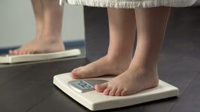 Το πρόσθετο βάρος, παχύ θηλυκό στο μπουρνούζι που στέκεται στις κλίμακες για να ελέγξει τη διατροφή οδηγεί στοκ φωτογραφίες