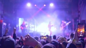 Το πρόσωπο ανεμιστήρων που παίρνουν το βίντεο και οι φωτογραφίες στο κύτταρο τηλεφωνούν στο κόμμα συναυλίας στο φως φιλμ μικρού μήκους