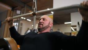 Το πρόσωπο ενός αθλητή που συμμετέχει σε μια αθλητική λέσχη, ασκεί στους θωρακικούς μυς 4K η αργή Mo απόθεμα βίντεο