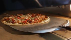 Το πρόσωπο κινηματογραφήσεων σε πρώτο πλάνο ανοίγει την πόρτα παίρνει έξω την ιταλική πίτσα από το φούρνο φιλμ μικρού μήκους