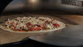 Το πρόσωπο κινηματογραφήσεων σε πρώτο πλάνο βάζει την ιταλική πίτσα στην πόρτα περίβολων φούρνων απόθεμα βίντεο