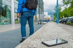 Το πρόσωπο ξεχνά το smartphone σε έναν πάγκο στην οδό στοκ φωτογραφία με δικαίωμα ελεύθερης χρήσης