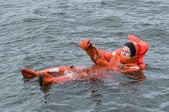 Το πρόσωπο που επιπλέει στον ιματισμό διάσωσης ανάβει handflare Στοκ Εικόνα