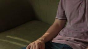 Το πρόσωπο σε έναν καναπέ αλλάζει τα κανάλια στον τηλεχειρισμό απόθεμα βίντεο